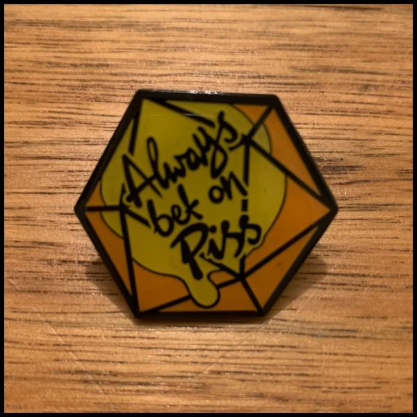 front image of the Always bet on piss pin